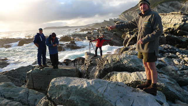 Chris Birmingham on a rugged, rocky coast with three others filming a television show.