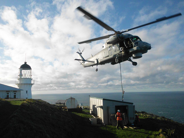 A dark grey Navy Seasprite helicopter lifts a new electricity generator on to the island beside a lighthouse.