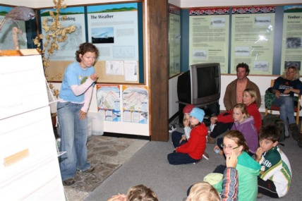 Jess Scrimgeour standing in front of a class of kids teaching them about conservation.
