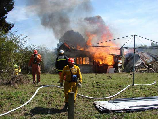Fire fighters battling a burning house.