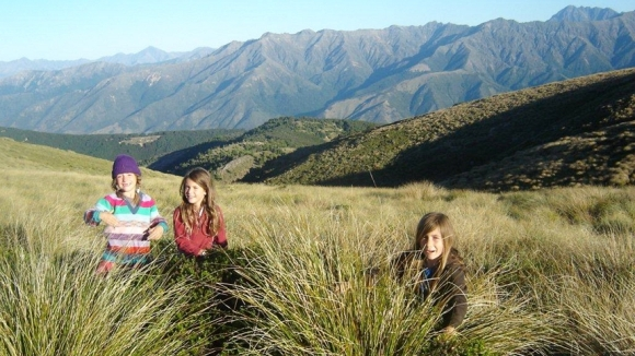 Zara, Paige and Emma sit amongst the tussock.
