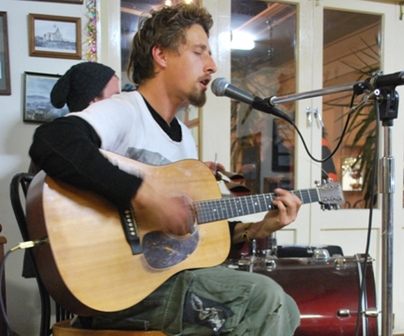 Oliver Knox performing music on his guitar.