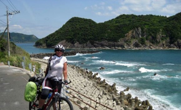 Gina standing by her bike by the water. Land in distance.