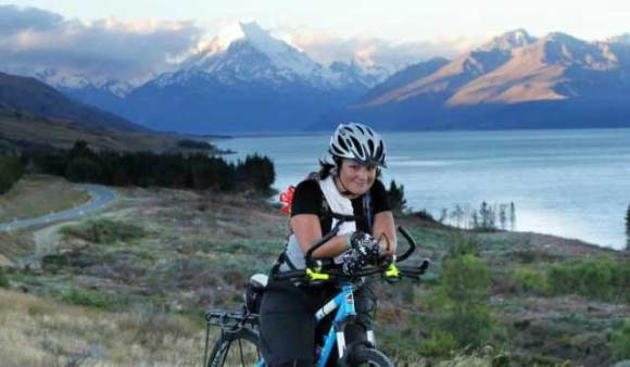 Gina on her bike, mountains in the background.