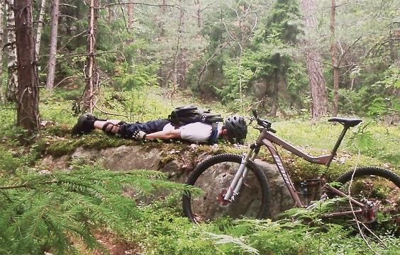 A mountain biker planking along a track.