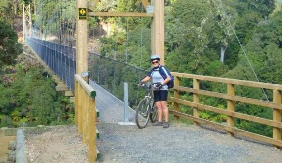 Wendy with her bike by a bridge on the Pureora Timber Trail.