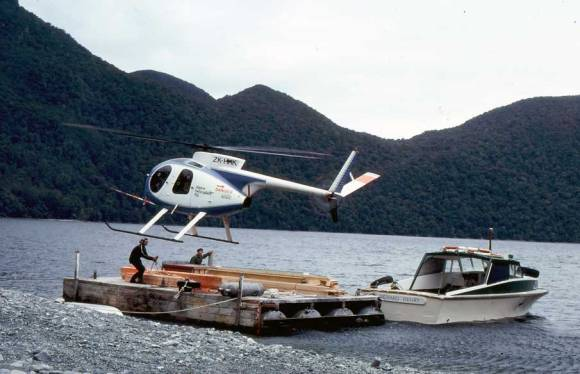 Helicopter lifting material during the mid 1970s from head of Lake Te Anau.