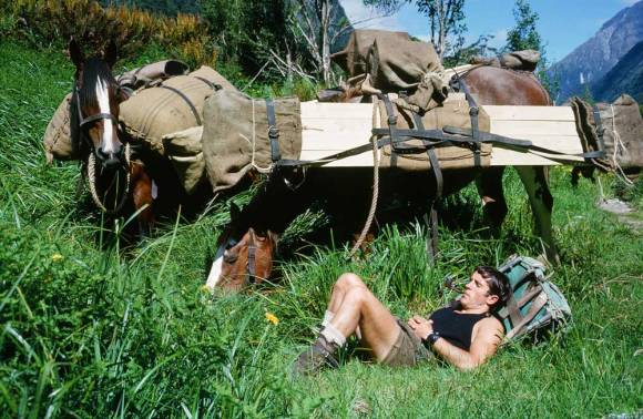 Ray Willett having a rest with his pack as a pillow. Horses in the background.