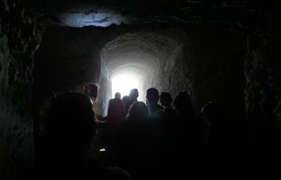 Students in a long, dark tunnel underground.