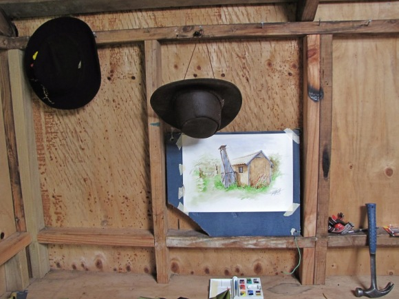 A watercolour paining of a hut hanging on the hut wall.