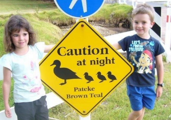 Twins Lucy and Jake beside a pāteke sign.