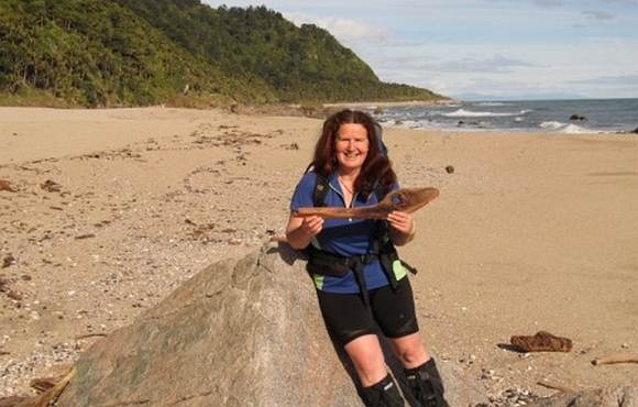 Maria with a piece of driftwood shaped like a fish at the beach.