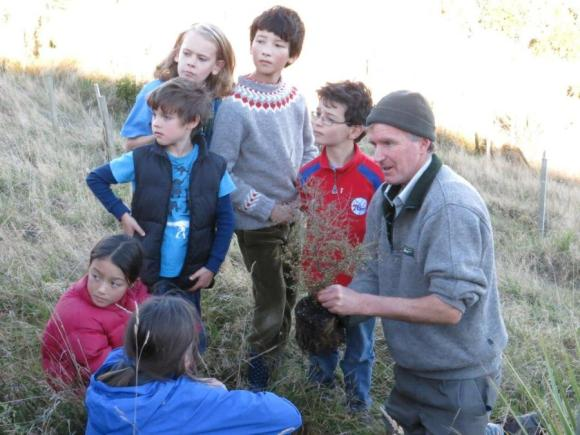 Ranger Jim Fyfe planting trees with the children.
