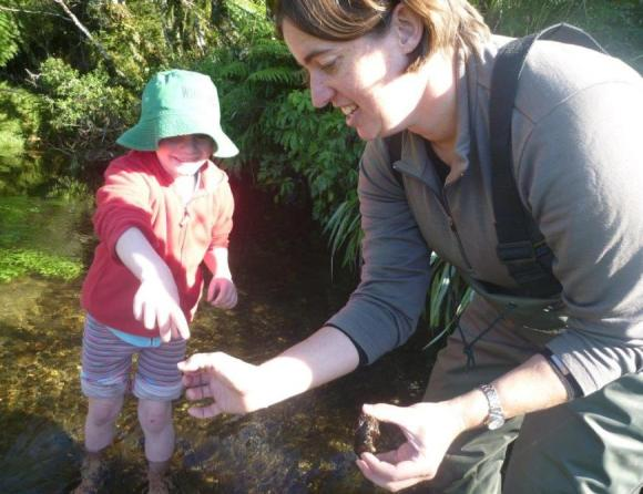 Cornelia standing in a stream with a school student looking for macroinvertebrates.