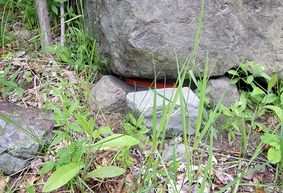 A geocache hidden at Rainbow Mountain under a rock.