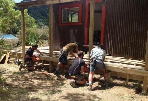 Builders finishing the deck around the hut/