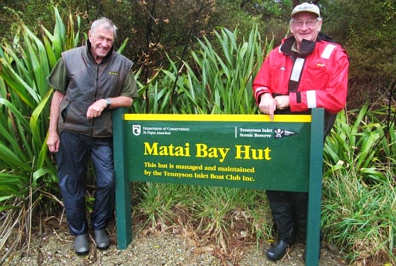 Club members standing by the Matai Bay Hut sign.