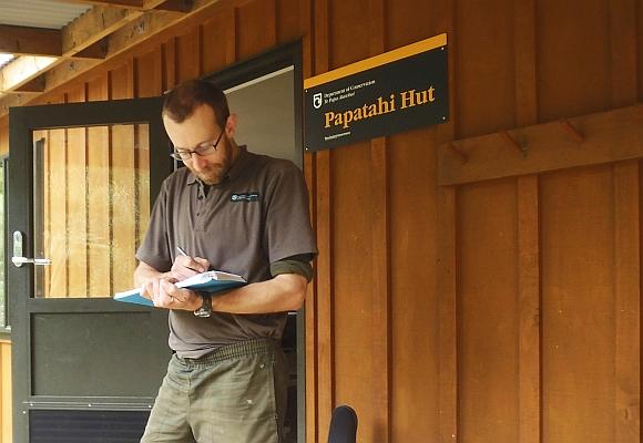 Ranger Daryl Stephens at Papatahi Hut checking off a list.