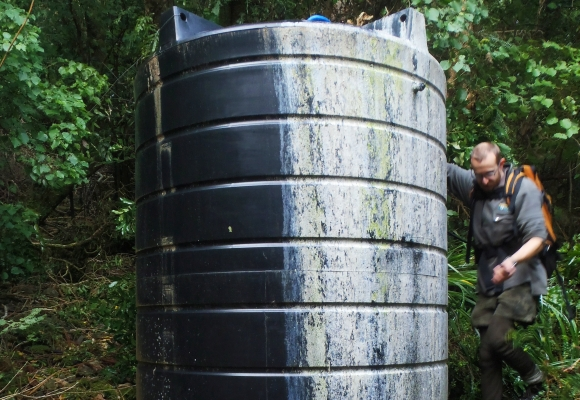 Ranger Daryl Stephens inspecting the water tank at a hut.