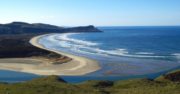 Looking north from near Cape Saunders past the mouth of Papanui Inlet to Victory Beach. Photo: Urlich Lange | CC BY-SA 3.0.