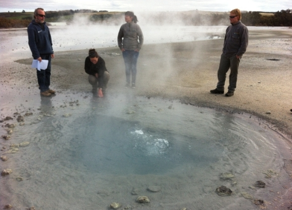 DOC rangers standing around a hot pool at Lake Rotokawa.