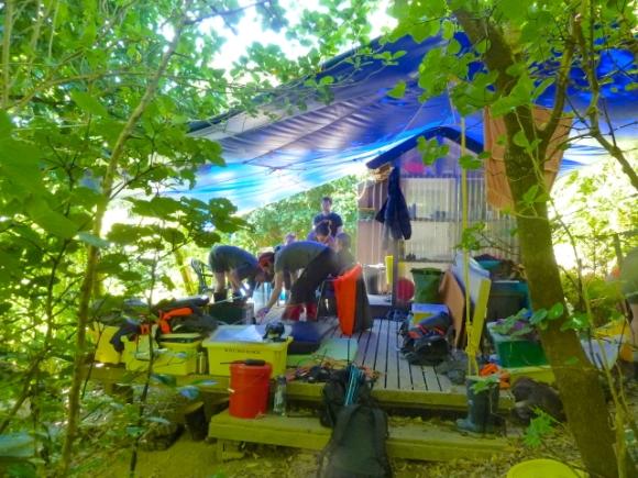 Organising under the tarpaulin at the tiny DOC hut.