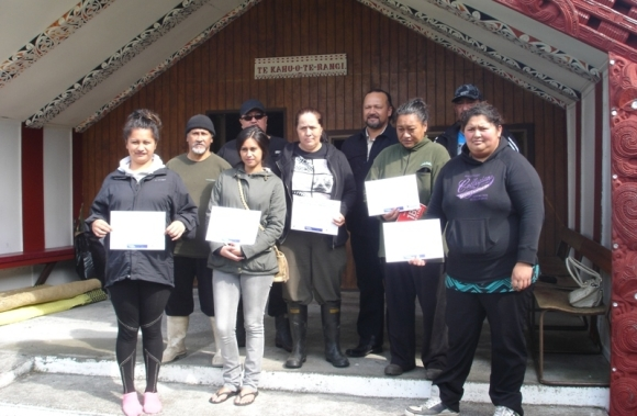 Students with certificates on graduation day.