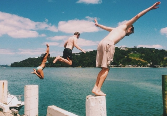 Daniel and friends jumping off a wharf into the sea.