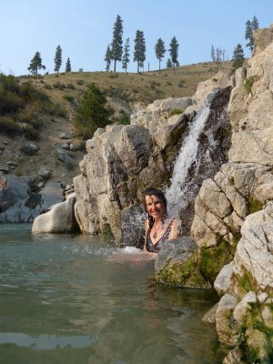 Sally sitting under a small waterfall in Kirkham Hot Springs.