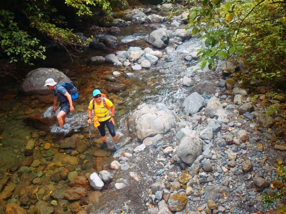 Trampers walking through Ohau River. Photo: Don Herron.