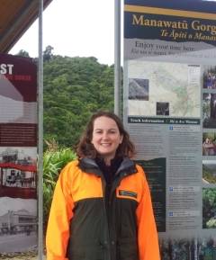 Chloe Barnes in front of a sign at the Manawatū Gorge.