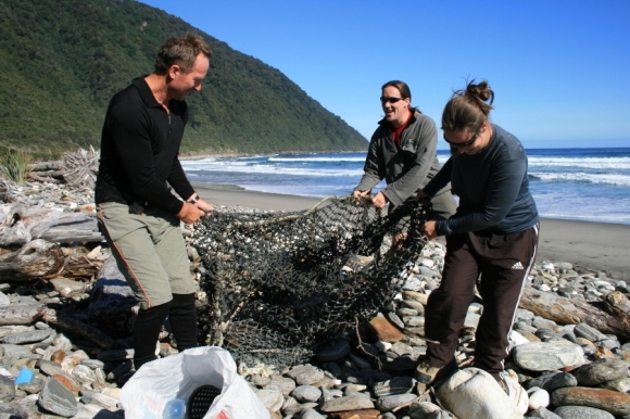 Volunteers and DOC staff clear a fishing net from the Fiordland coast. Photo: Shirley Whyte ©.