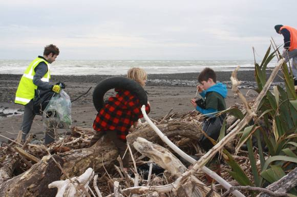 Beach clean-up volunteers with a car tyre. Photo: Taranaki Conservationists.