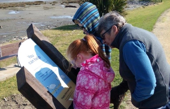 Reading a new sign at the Manawatu Estuary.