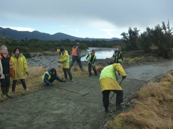 Conservation Volunteers New Zealand volunteers raking the new track.