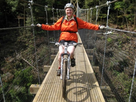 Alicia Warren on a bridge while cycling the Pureora Timber Trail.