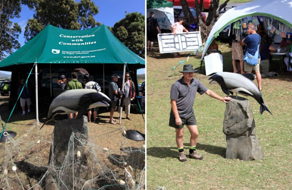 DOC ranger with the dolphin statue at Māui Dolphin Day.