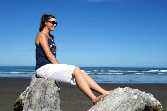 Karlene sitting on a rock at Himatangi beach.