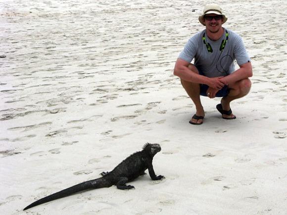 Peter beside a marine iguana on a beach in Galápagos