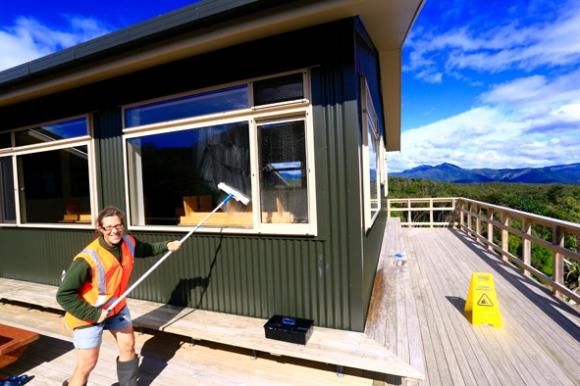 Anja cleaning the outside of a hut on the Heaphy Track.