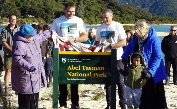 Duane and Adam, Minister Nicky Wagner and Peg Whitton for iwi unveil the DOC sign marking the beach becoming national park. Photo Trish Grant.