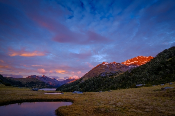 The evening sun dips below the horizon, casting its last red light upon the mountains surrounding Lake Roe Hut. Credit: © Crystal Brindle.